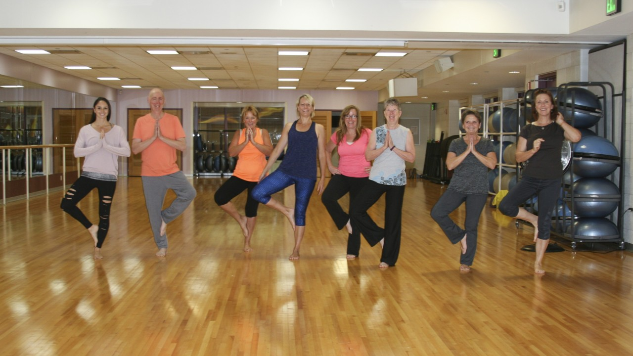 Yoga fitness class with Western Wellness participants doing a tree pose
