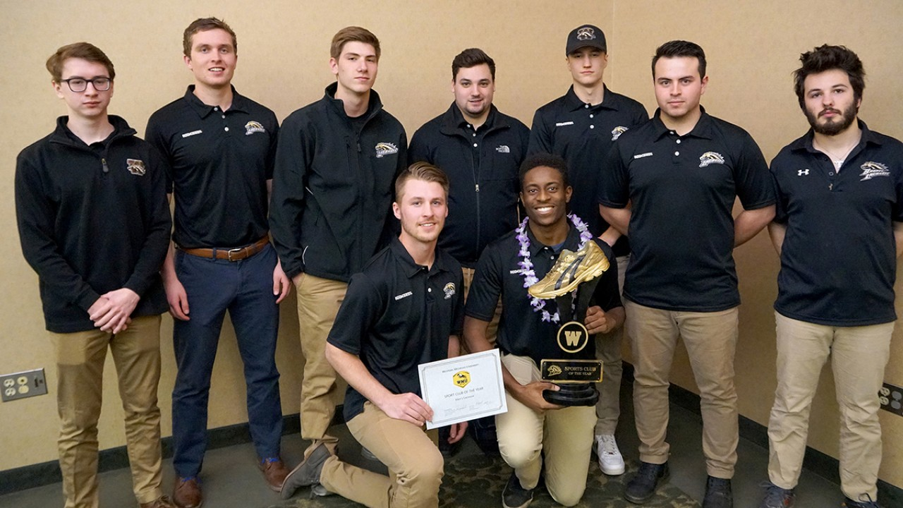 Men's Lacrosse Club Sport of the Year 2017-18, mixed group of men all in black shirts and khaki pants. One in front with certificate and the other is holding a trophy.