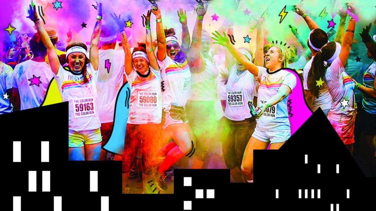 people running and smiling in the color run race with colored powder in the air and a graphic image of a cityscape in front of the runners