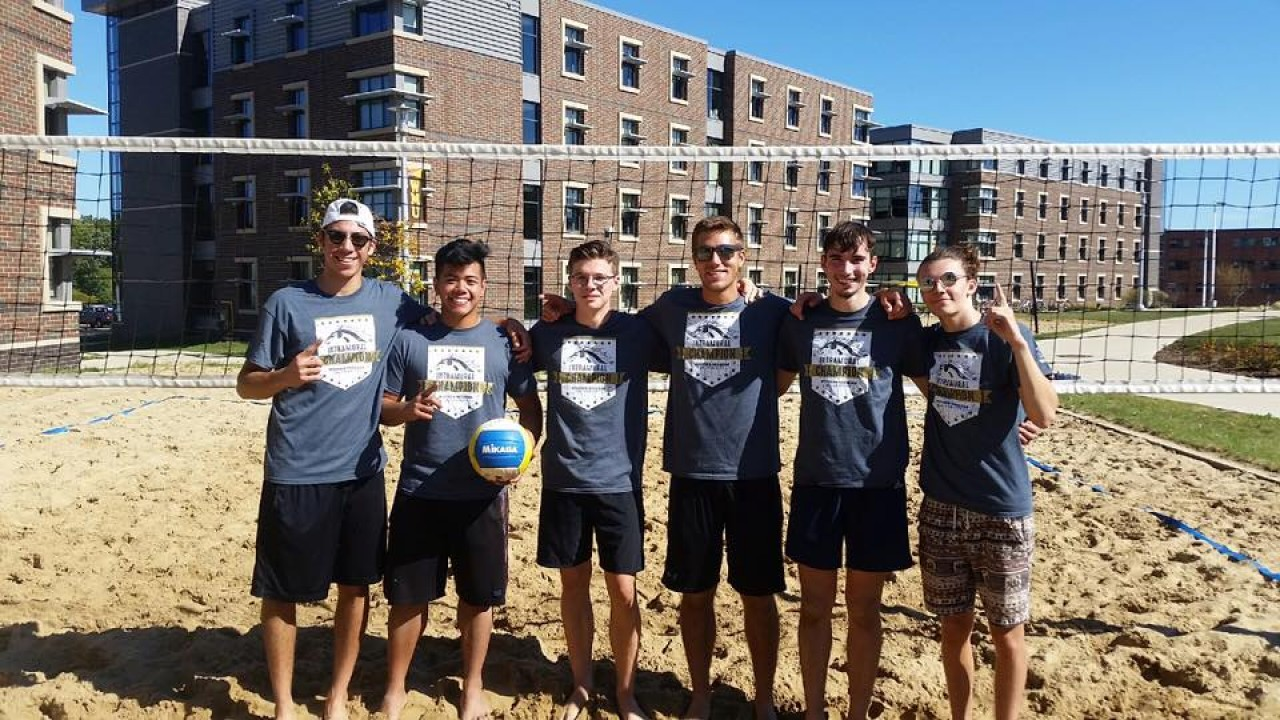 Intramural sand volleyball team standing in front of the net