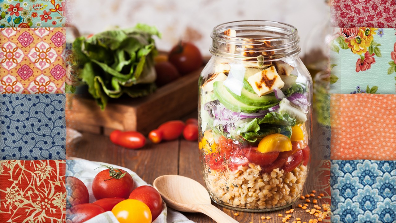vegetables all stacked in a mason jar with a spoon, vegetables and a cutting board with a patchwork quilt as a background
