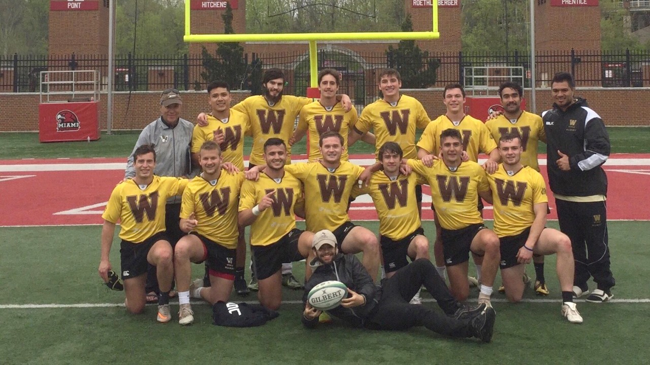 Mens Rugby team in front of final score board winning the MAC title