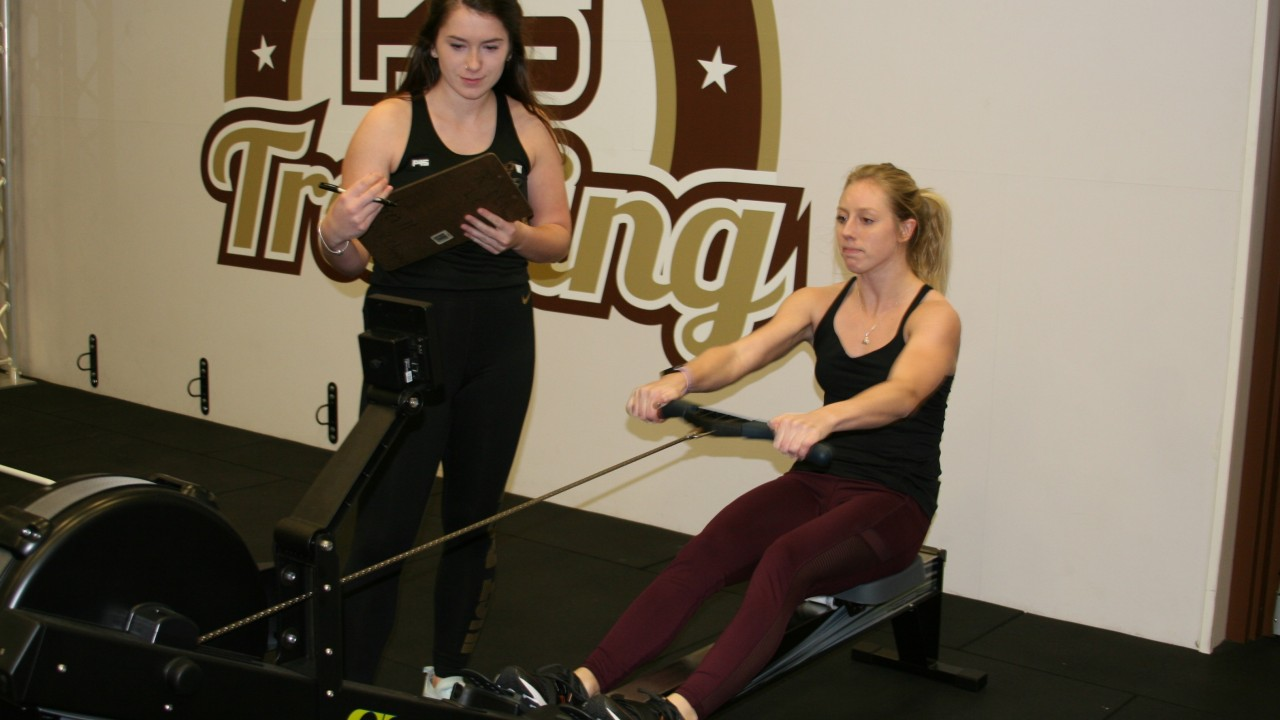 Participant on rowing machine with an F45 trainer encouraging them