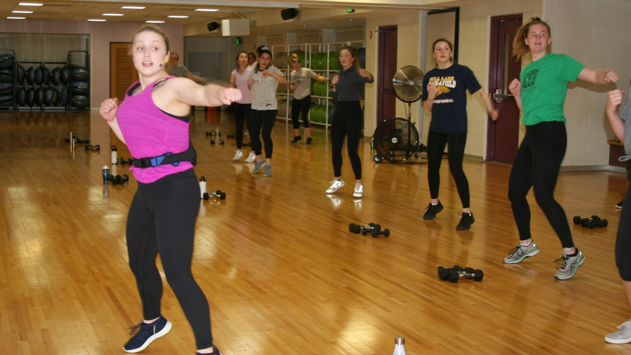 Molly teaching a kick and tone class with participants behind her
