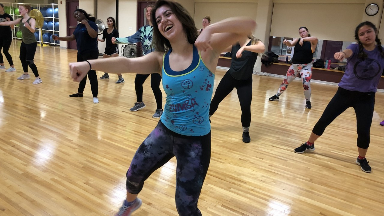 Emma teaching zumba with participants behind her