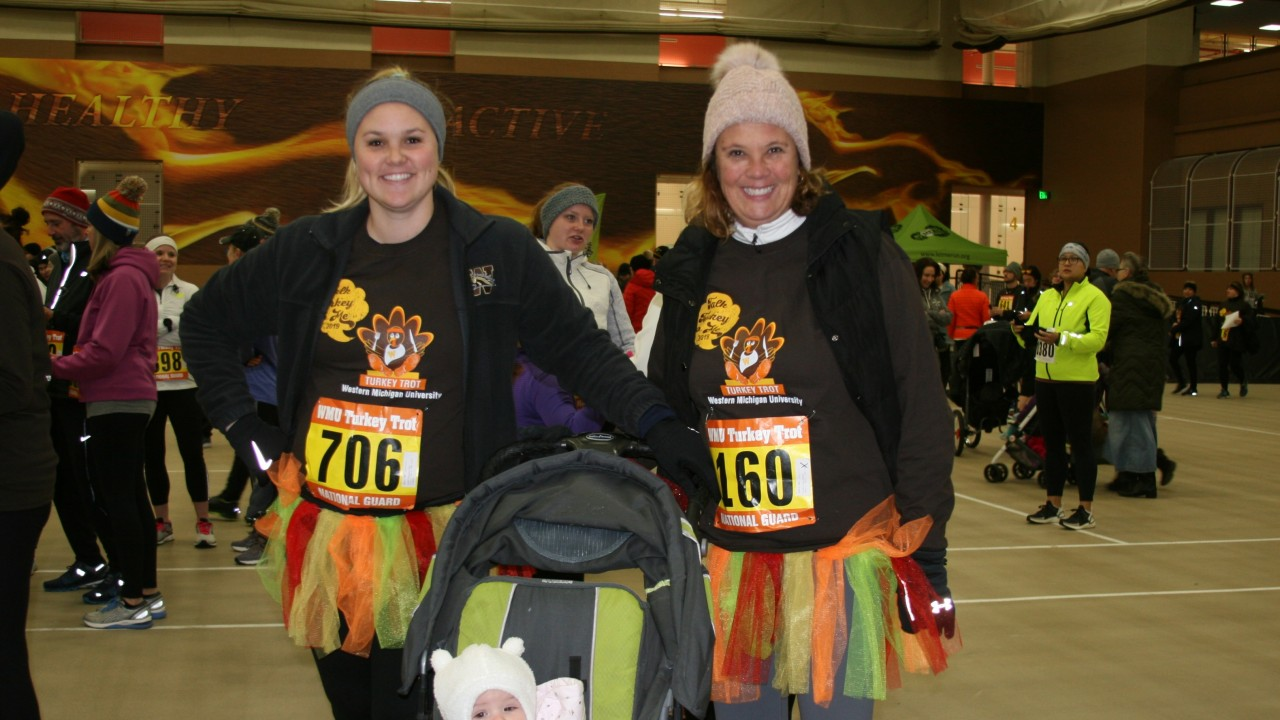 Turkey Trot participants dressed up in Turkey Trot shirts, tutus and baby in a stroller
