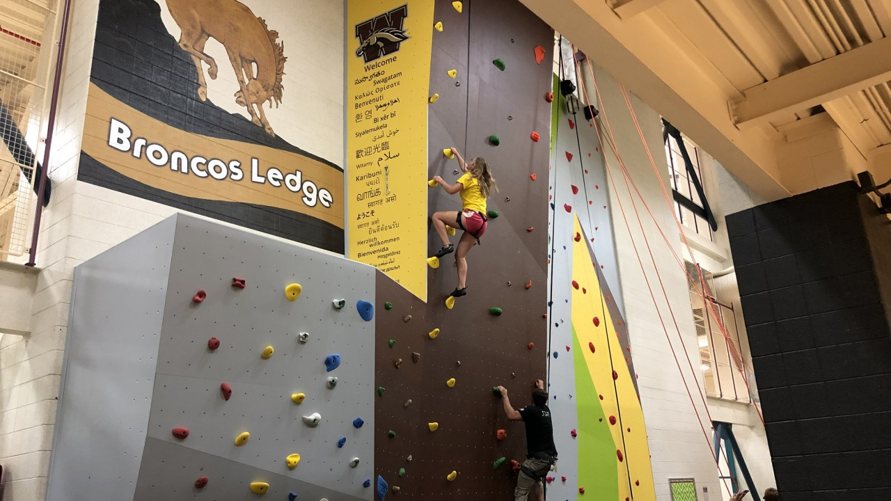 Participant in a yellow shirt and red shorts climbing the side of the wall