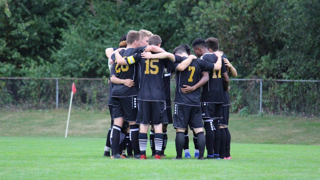 Group of men's soccer club all embracing in a huddle in their team uniforms