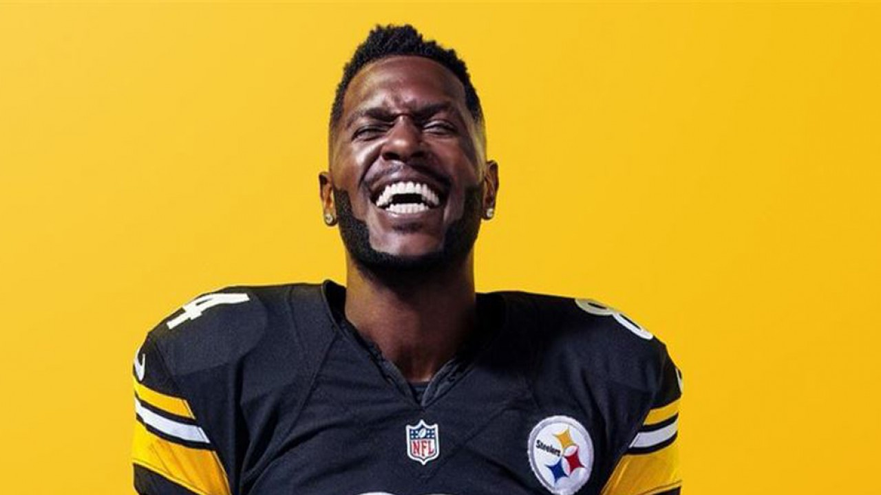 Football player grinning with yellow background behind him for Madden 19 tournament