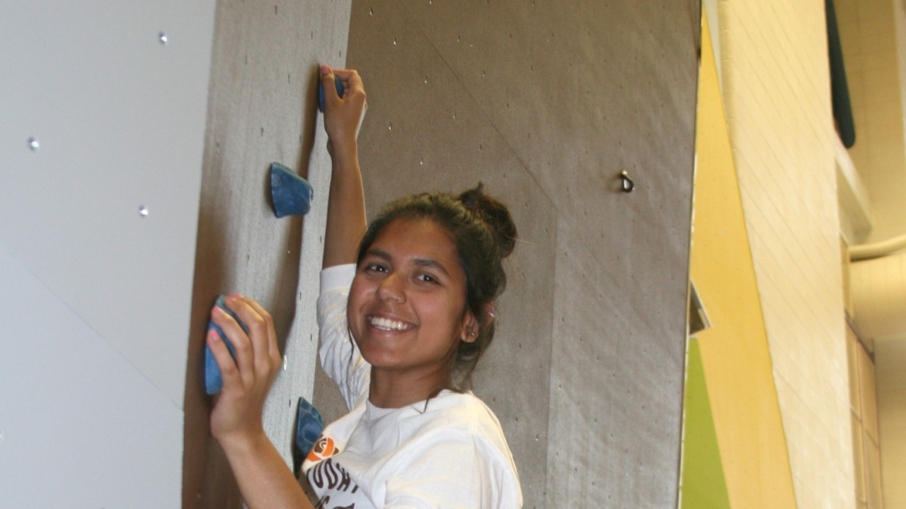 International student of diversity smiling and climbing the new climbing wall