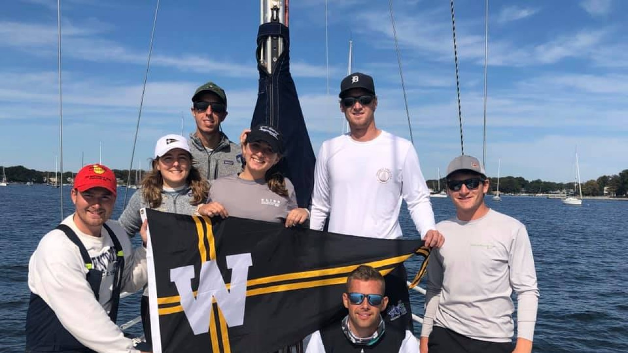 Mixed group of people in the Sailing Club, on a boat with water surrounding them and holding a WMU flag
