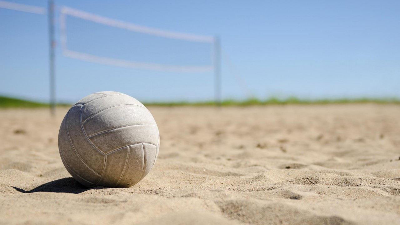 Volleyball sitting in the sand with a volleyball net and blue skies behind it