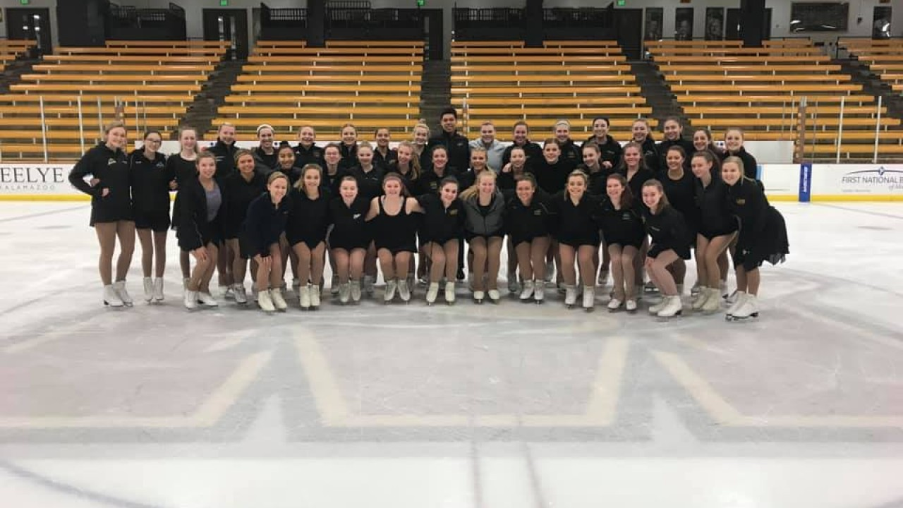 Skating club team photo. Entire time in black wearing their skates and on the ice posing together with coaches