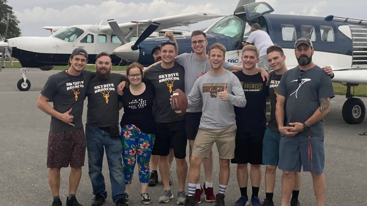 The Sky Dive Broncos club standing in front of a plane