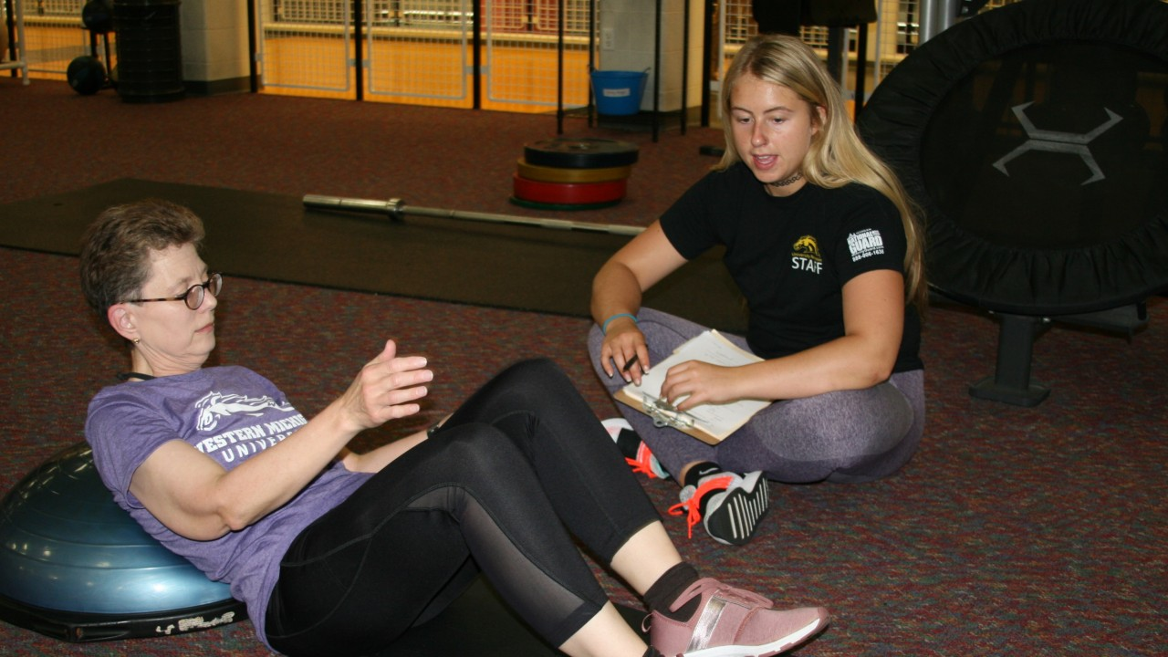 Personal trainer, Taylor with a female client who is working on her sit ups.