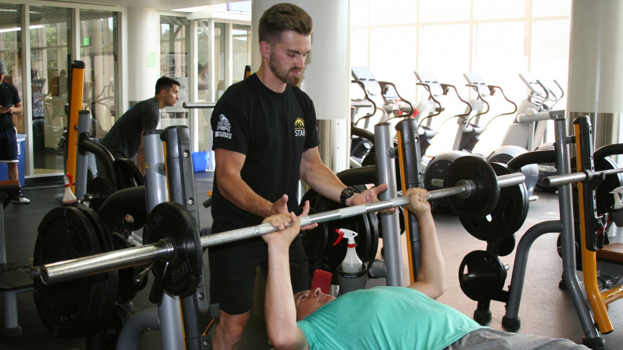 Personal training, Logan working with a client in the weight room