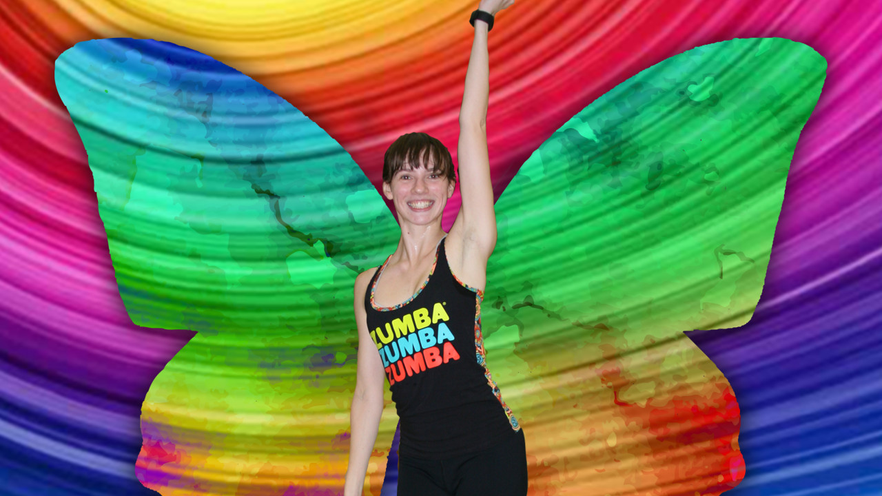 Maddy with a Zumba top on and arm straight up in the air dancing with bright colors and butterfly wings behind her