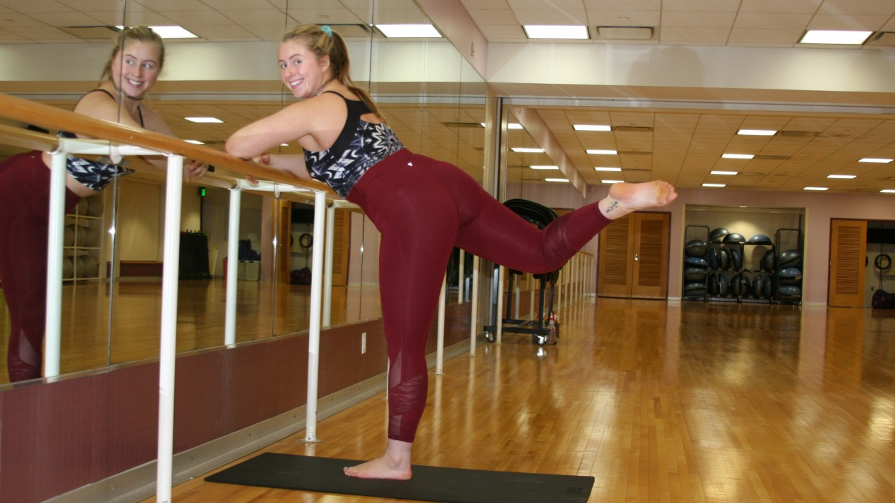 Fitness instructor, Taylor doing a barre pose on the bar in aerobics room