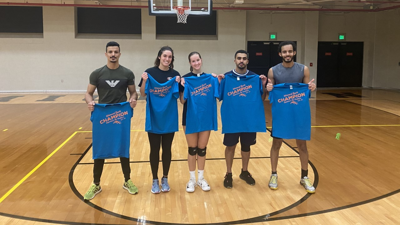 Mixed group of volleyball players with their champion shirts