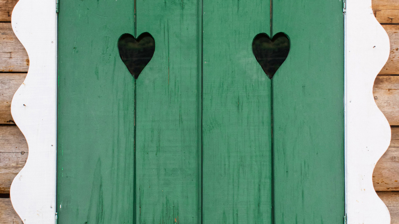 Bavarian style green shutter with hearts in it and white trim