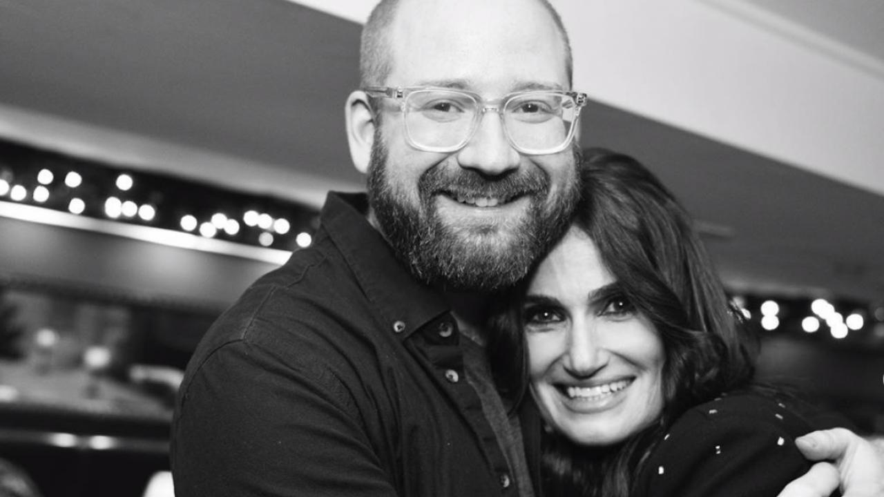 Black and white photo of David Alpert hugging Idina Menzel.