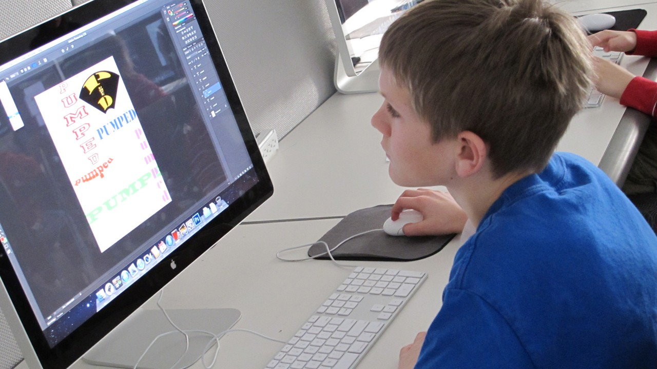 young student working on computer creating a graphic design