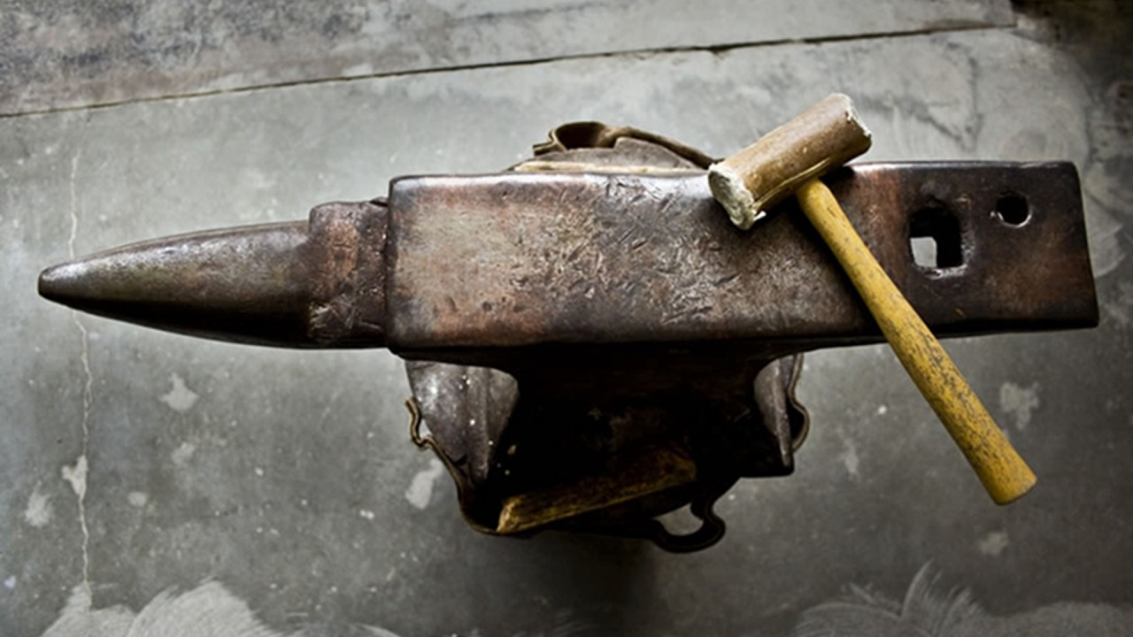 overhead of a hammer over an anvil