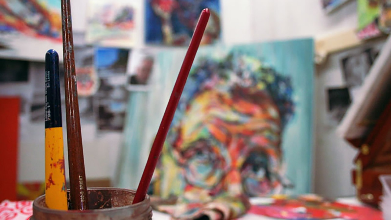 paint brushes with paintings behind it