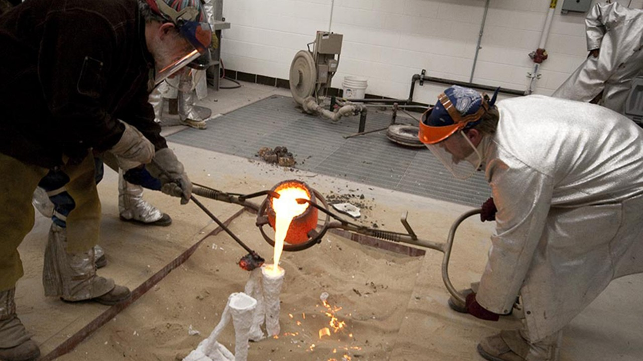 students pouring metal into molds