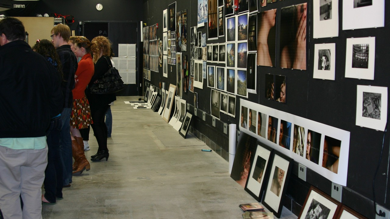 people at a gallery full of prints and photography on display