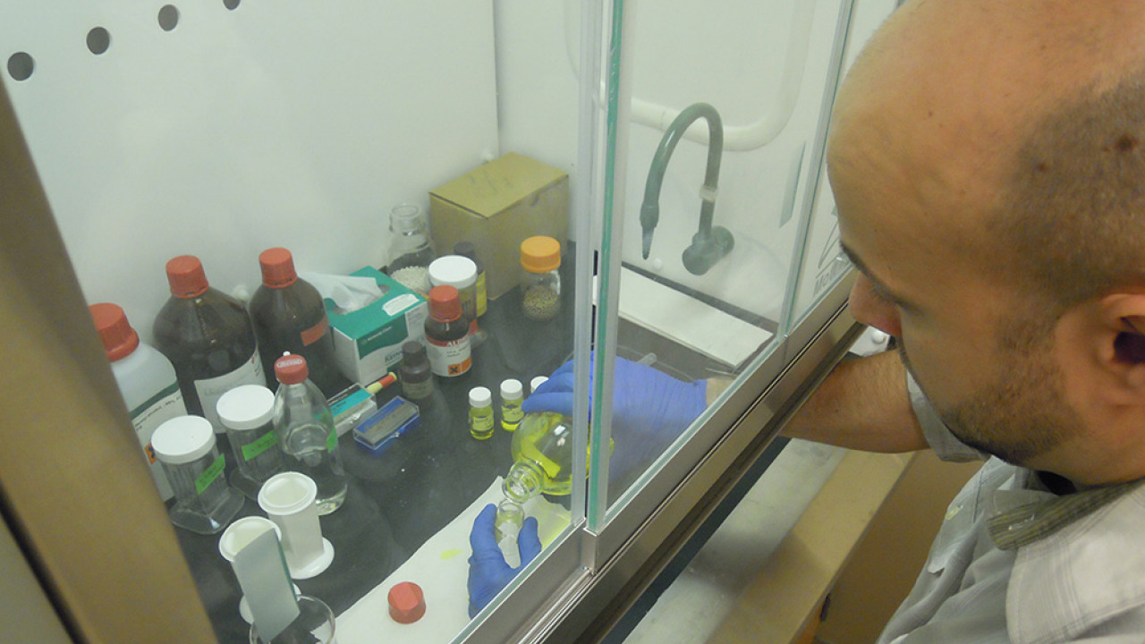 student adding chemicals under the fume hood