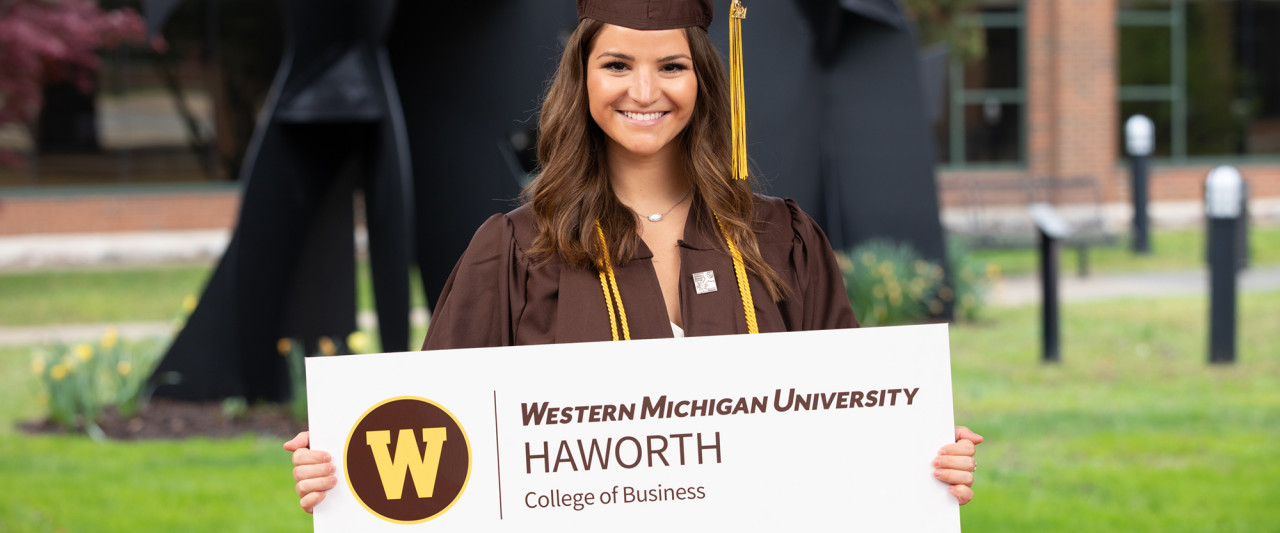 Pictures is Olivia Langdon in a cap and gown holding a WMU Haworth College of Business sign