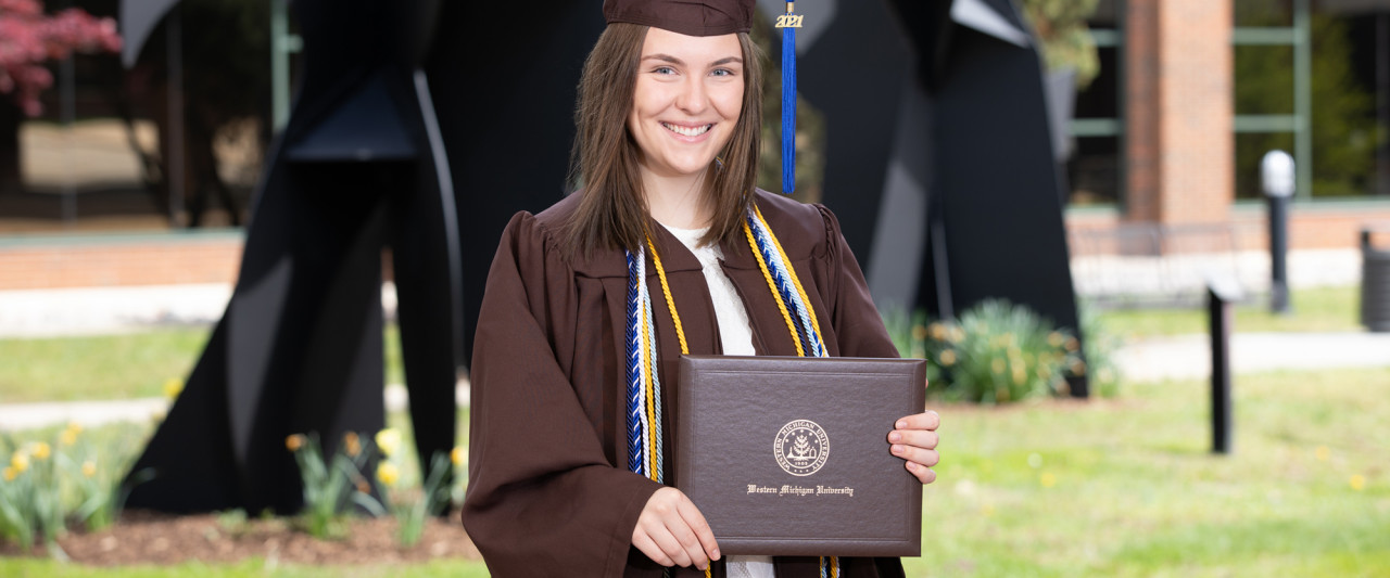 Pictured is Sarah Reynolds wearing a cap and gown and holding her degree