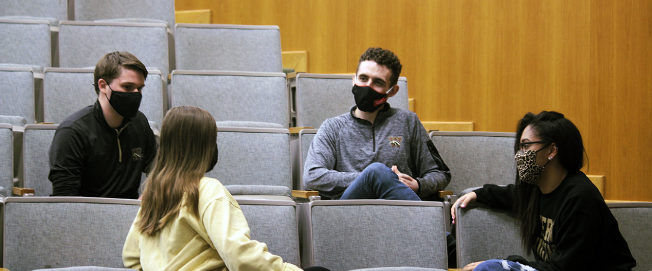 Pictured is a group of masked students, socially distanced, sitting in an auditorium