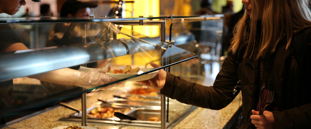 Student getting plate of food at Valley Dining Center