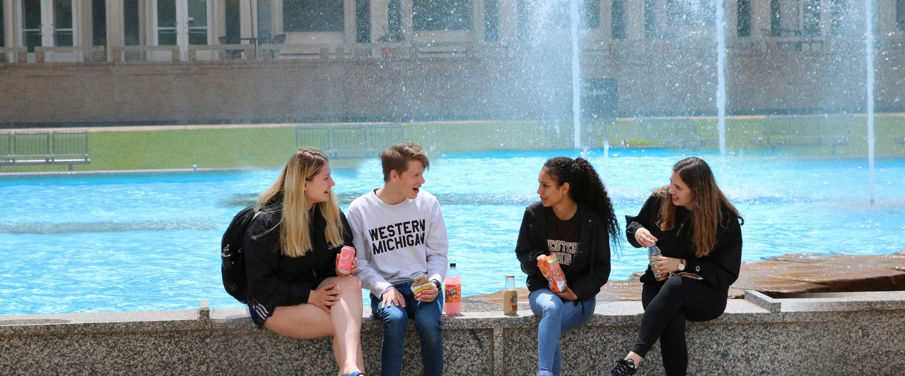 Four students sitting on the edge of the fountain in front of Plaza Cafe