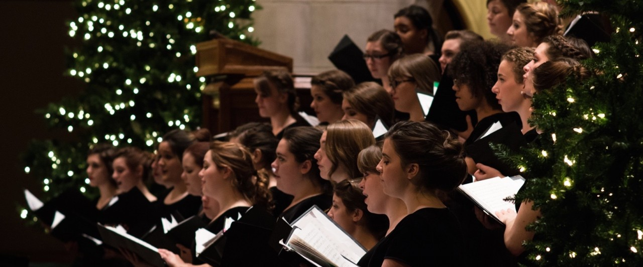women's choir performing in First Presbyterian Church amidst Christmas tress