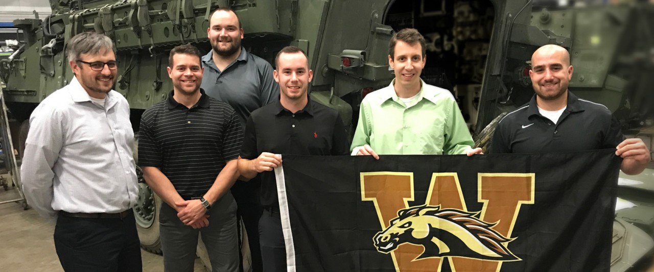 photo of WMU ISM alumni and intern holding Western flag