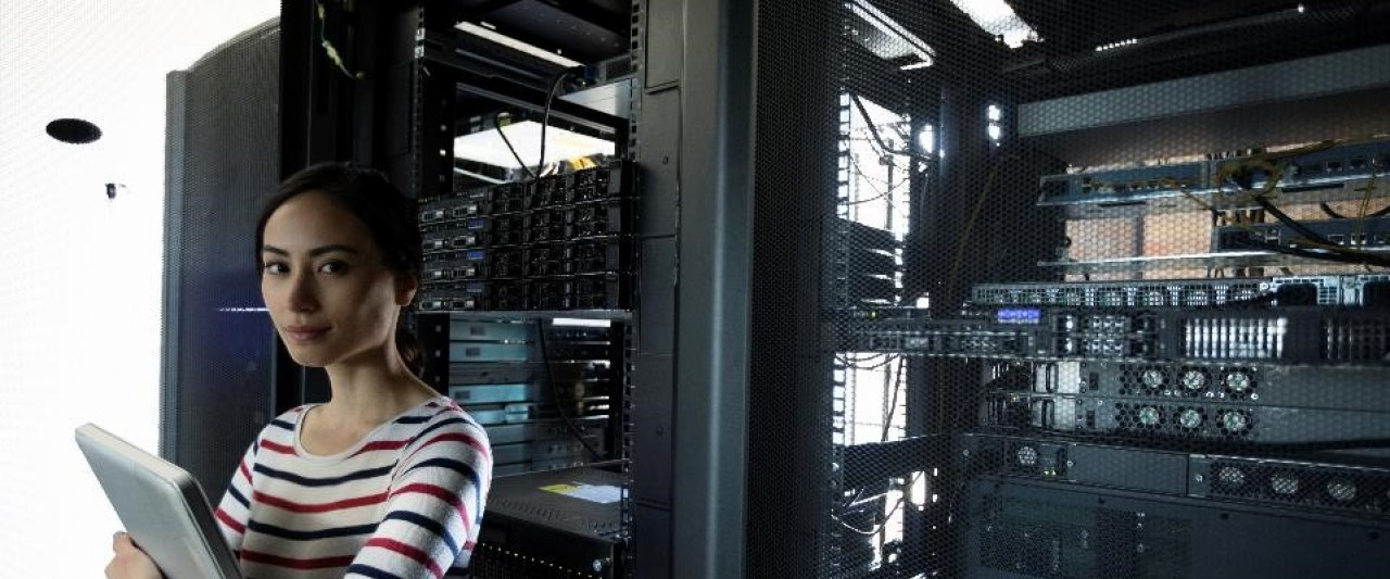 Woman with computer in server room.