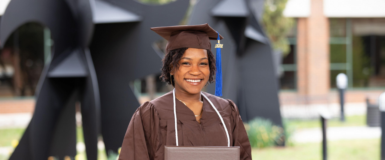 A finance student, smiles and poses with their diploma.