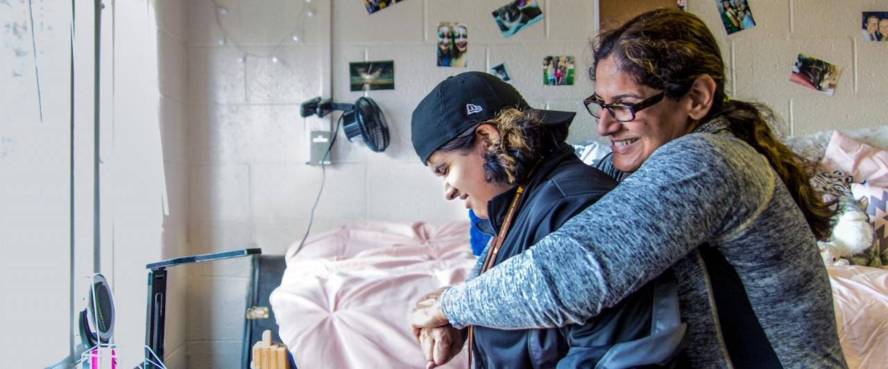 Parent hugging student in residence hall room