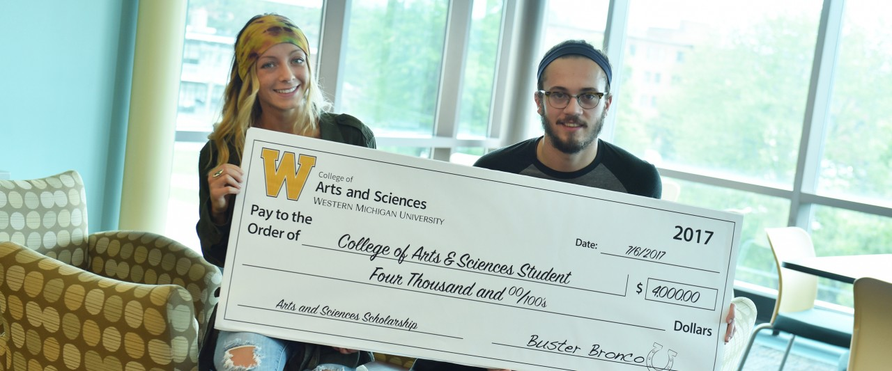 Two students who received a surprise retention scholarship of $4,000 hold up a fake check