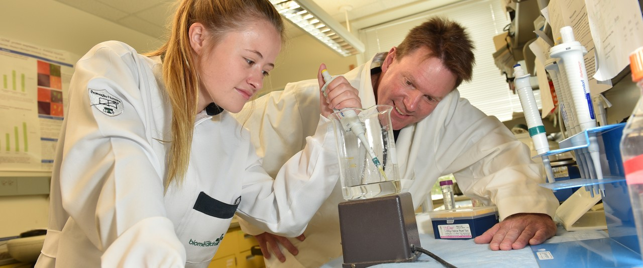A student and faculty member test the water in a beaker in a research lab
