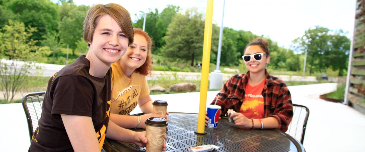 Three students sitting at table outside of the Valley Dining Center.