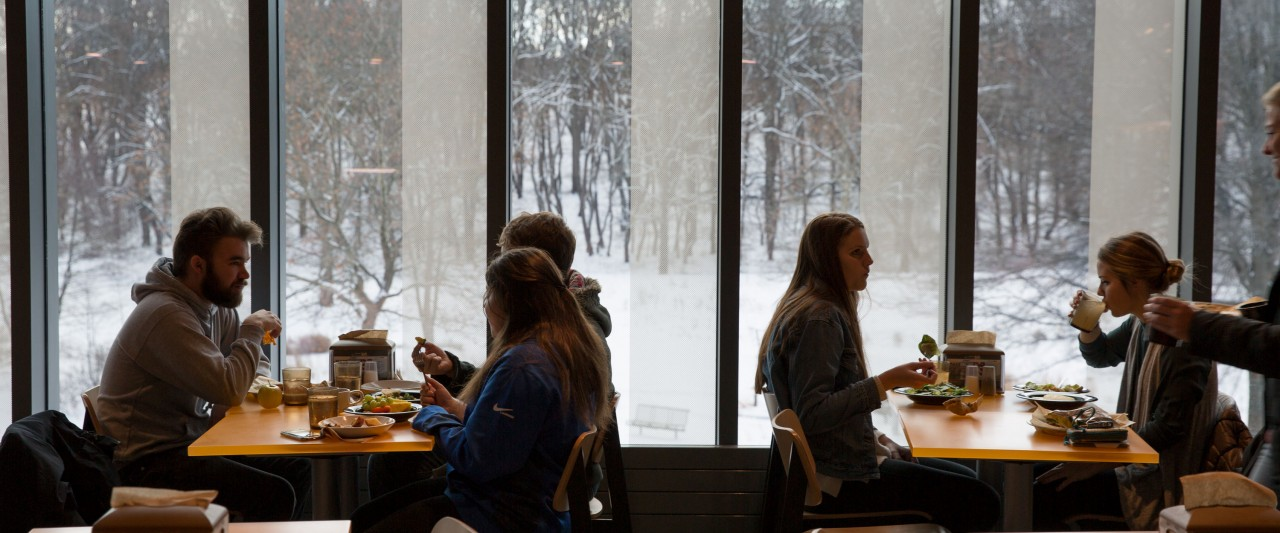 Students eating in front of large windows overlooking the snow.