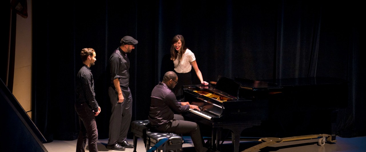Group of four jazz students performing on stage, singing and playing piano.