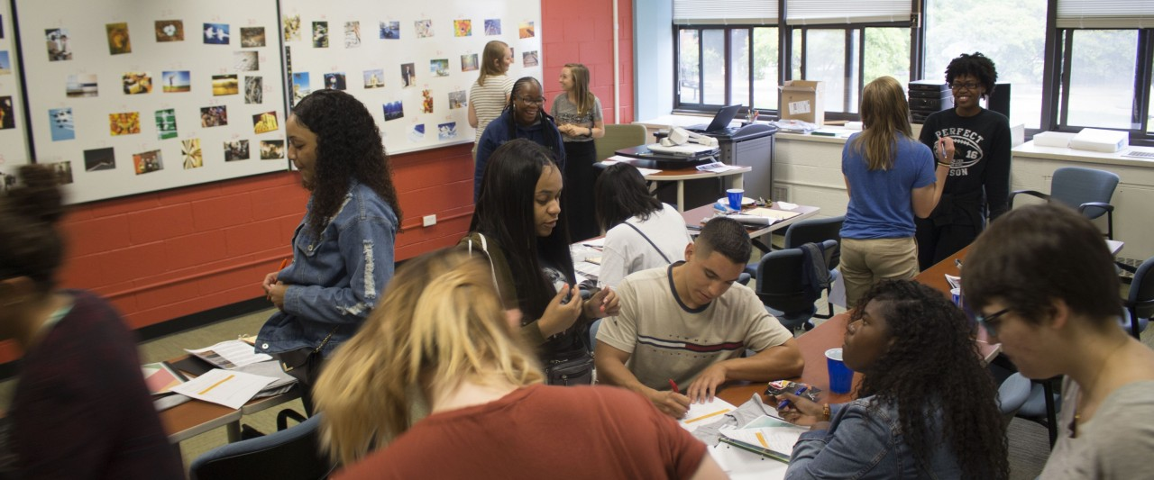 Several small groups of students working together in the same room.