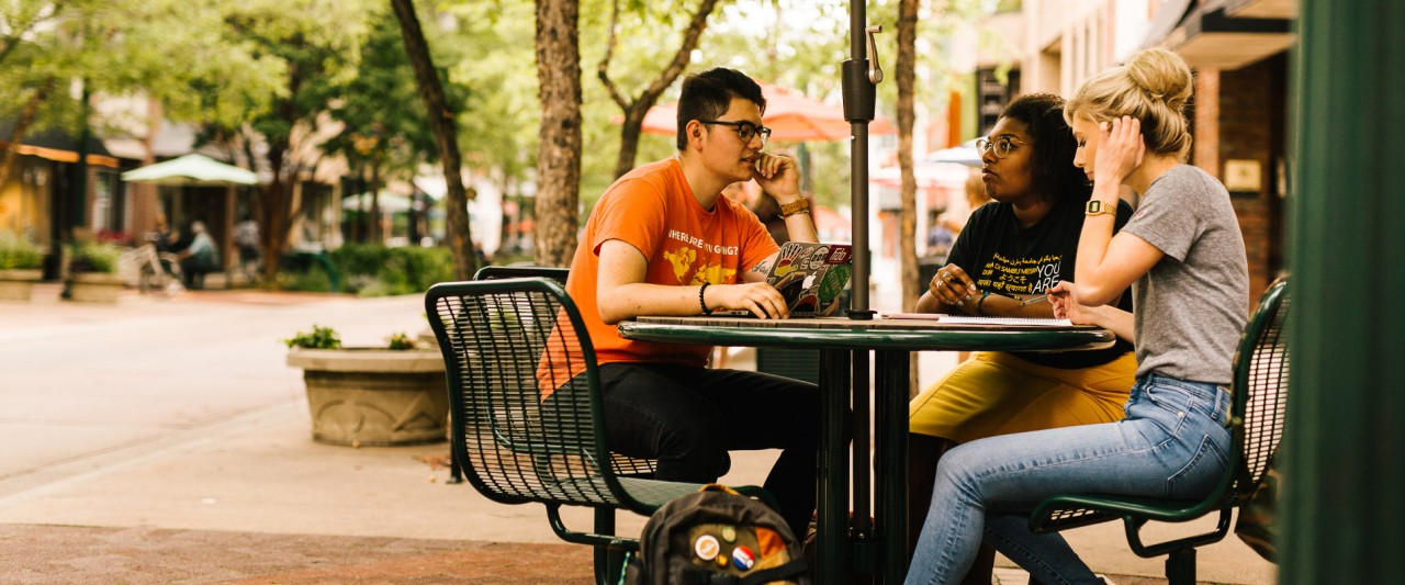 3 students sitting at an outdoor table in downtown Kalamazoo