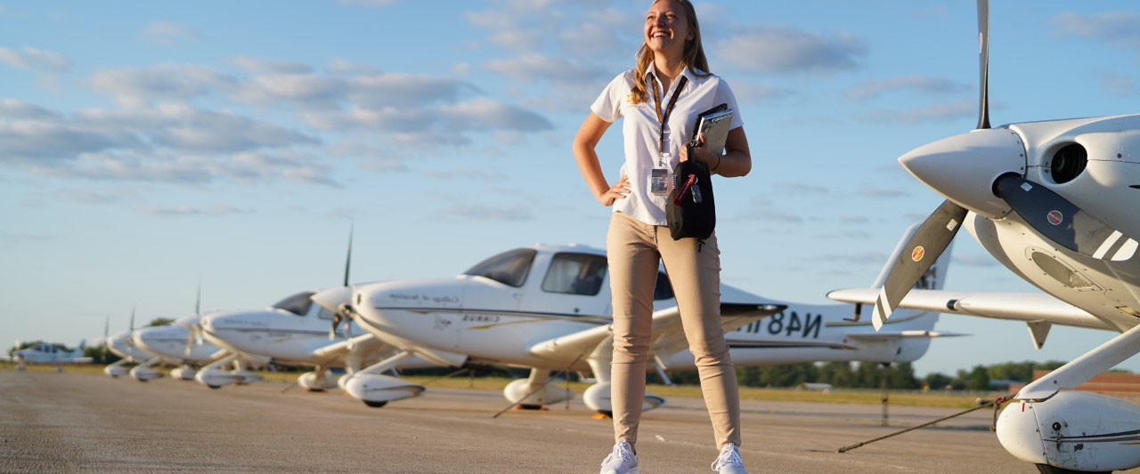 Lauren Quandt, an alumna and certified flight instructor at WMU, stands near several planes on the College of Aviation campus.