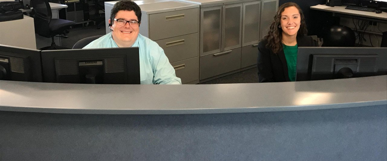 Two employees sit at a desk behind computers with cabinets and more computers behind them